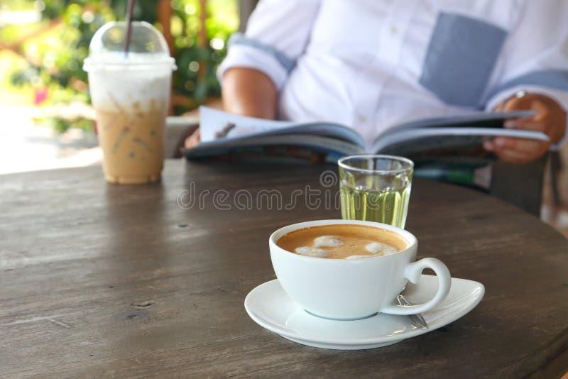 Sjuklig livsstil av den överviktiga damen som dricker kallt kaffe, medan läsa tidskriften i kafét royaltyfri bild