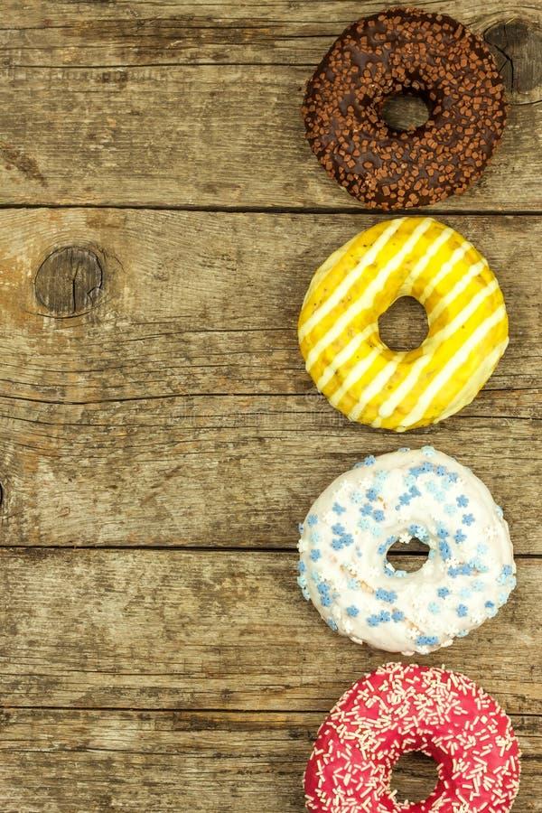 sjuklig mat Donuts på en trätabell Faror av fetma och sockersjuka Försäljningar av sötsaker Donuts för frukost arkivfoto