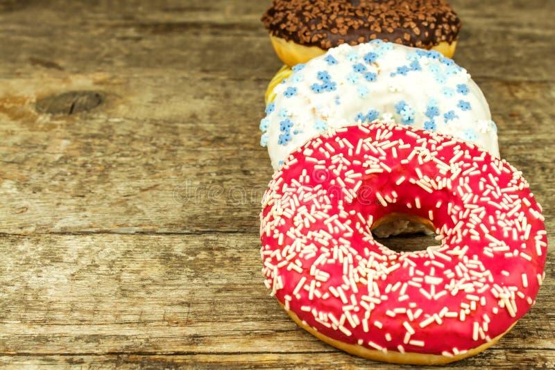 sjuklig mat Donuts på en trätabell Faror av fetma och sockersjuka Försäljningar av sötsaker Donuts för frukost royaltyfri fotografi