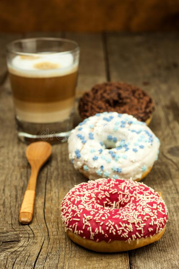 sjuklig mat Donuts på en trätabell Kaffe till efterrätten Faror av fetma och sockersjuka Försäljningar av sötsaker Donuts för fotografering för bildbyråer
