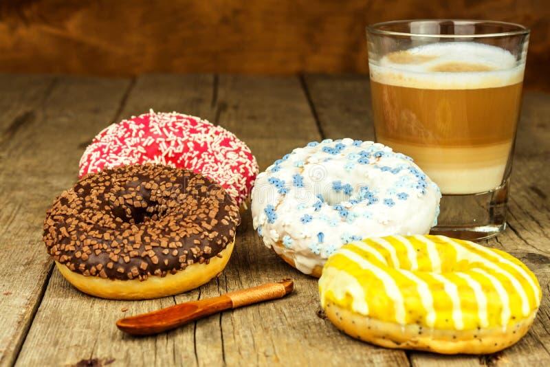 sjuklig mat Donuts på en trätabell Kaffe till efterrätten Faror av fetma och sockersjuka Försäljningar av sötsaker Donuts för royaltyfri foto