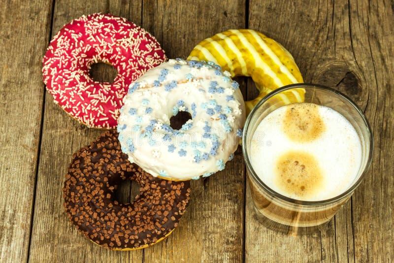 sjuklig mat Donuts på en trätabell Kaffe till efterrätten Faror av fetma och sockersjuka Försäljningar av sötsaker Donuts för arkivfoto