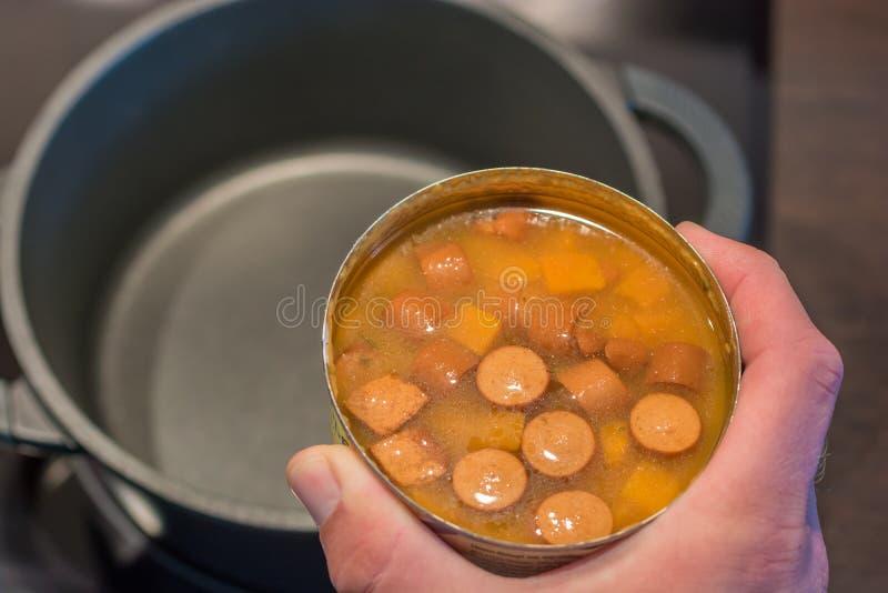 Sjuklig på burk soppa värmas i en kruka arkivfoton