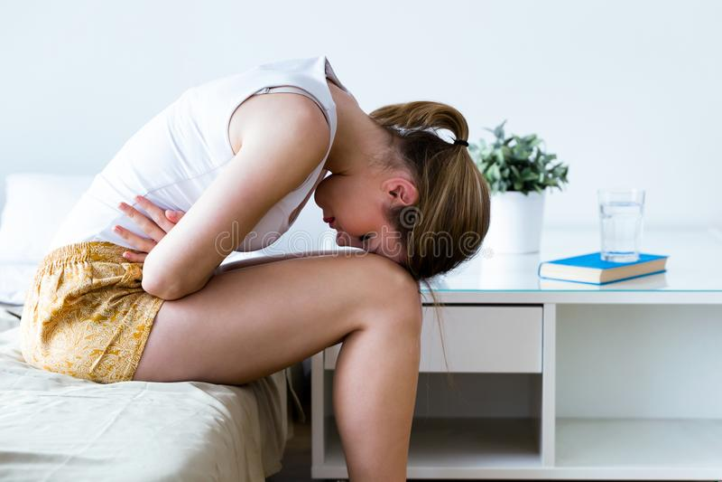 Sjuklig ung kvinna med magknipbenägenhet på sängen hemma arkivfoto
