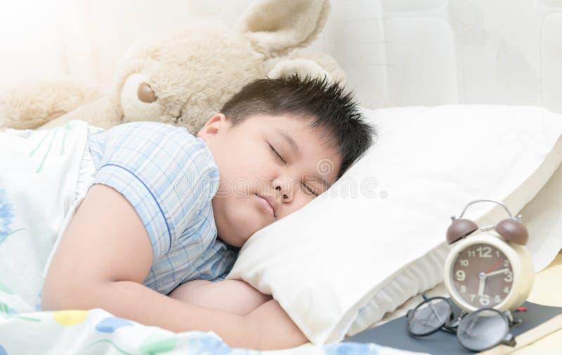 Sjukligt fet fay pojkesömn på säng arkivbilder