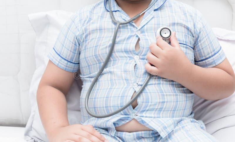 Sjukligt fet fet pojkekontrollhjärta vid stetoskopet fotografering för bildbyråer