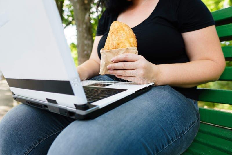 Sjukligt fet kvinna med för avhämtning bakelsemaskinskrivning på bärbara datorn arkivfoto