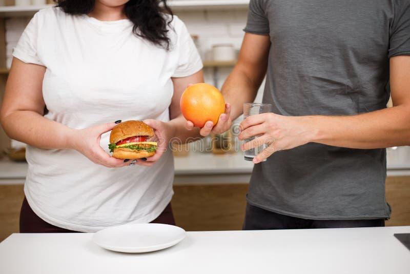 Sjukligt fet kvinna med hamburgaren och instruktören med frukter royaltyfria foton