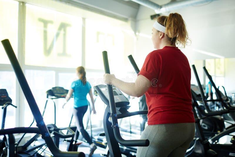 Sjukligt fet kvinna som utarbetar genom att använda ellipsmaskinen i idrottshall royaltyfri bild