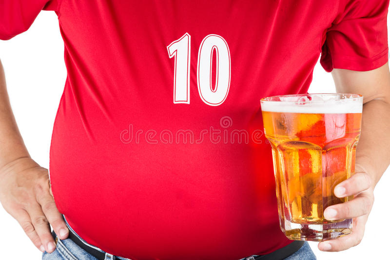 Sjukligt fet man med den stora buken som rymmer ett exponeringsglas av uppfriskande kallt öl fotografering för bildbyråer