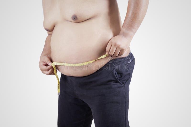 Sjukligt fet person som mäter hans buk 2 arkivbilder