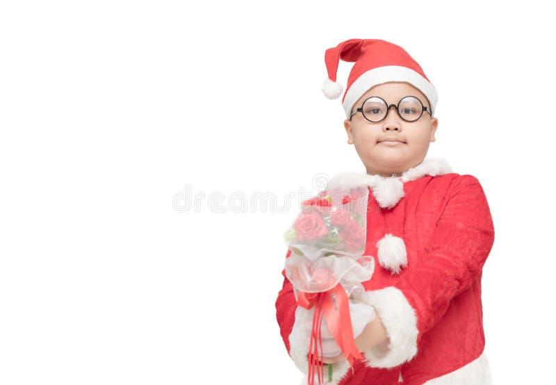 Sjukligt fet pojke i rosa bukett för Santa Claus dräktinnehav royaltyfria foton