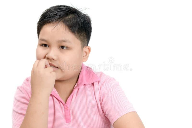 Sjukligt fet fet pojke som biter för att spika isolerat fotografering för bildbyråer