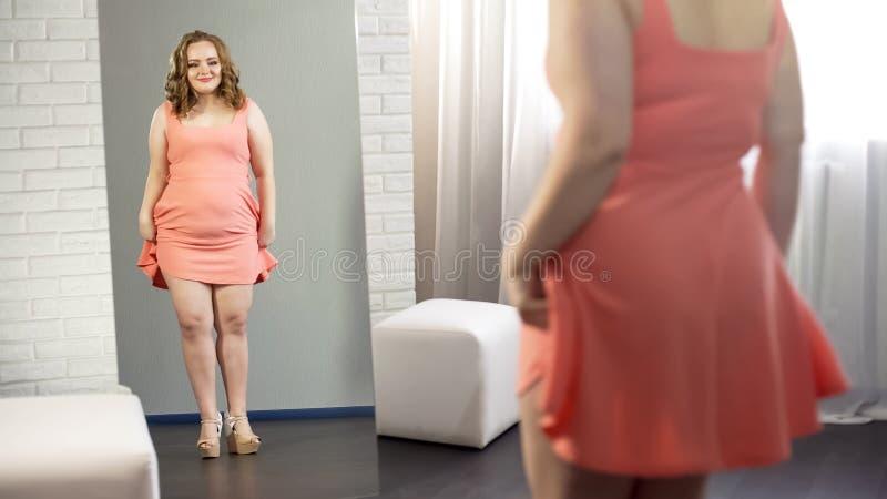 Sjukligt fet ung dam som ser hennes ben i mini- klänning, kropppositivity, övervikt royaltyfria bilder