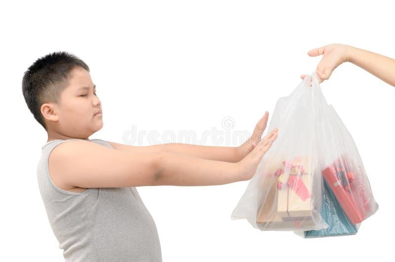 Sjukligt feta pojkeavskräden som mottar plastpåsar arkivbild