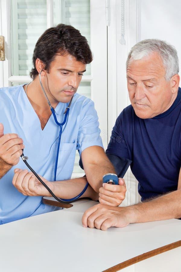 Sjukskötare Checking Blood Pressure av en hög man arkivfoto