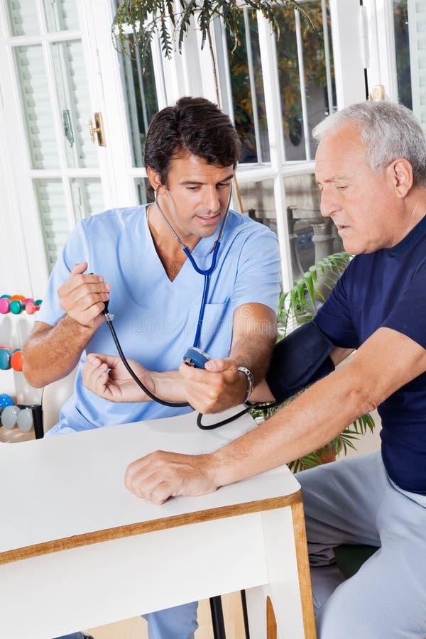 Sjukskötare Checking Blood Pressure av en pensionär arkivbilder