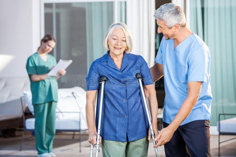 Sjukskötare Helping Senior Woman som använder kryckor arkivbild