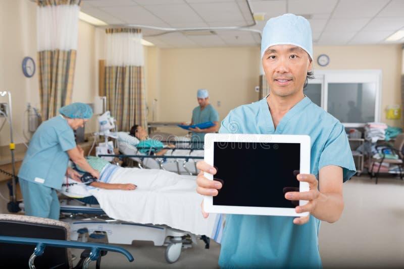 Sjukskötare Showing Digital Tablet i sjukhussal royaltyfri bild