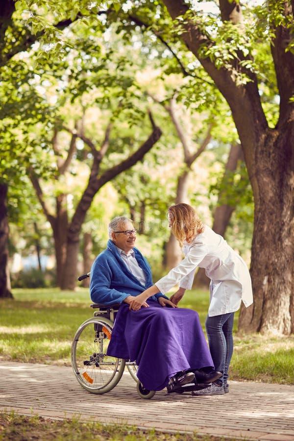 Sjukskötare som hjälper den höga mannen i rullstol royaltyfri bild