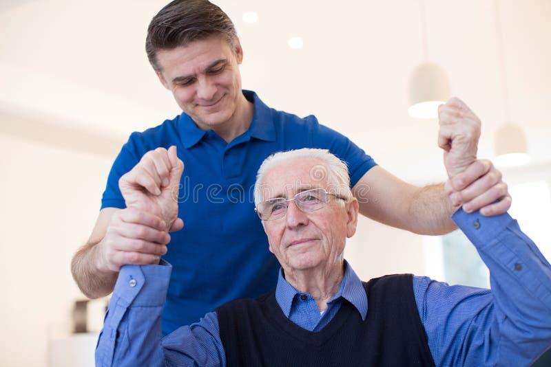 SjukskötareAssessing Senior Stroke offer, genom att lyfta armar arkivfoton
