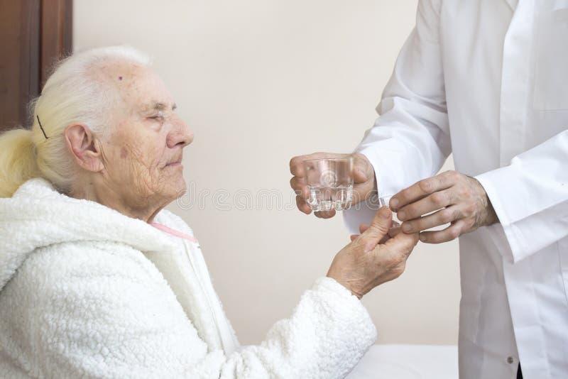 Sjukskötaren ger ett exponeringsglas av mediciner och ett exponeringsglas av vatten till en gammal kvinna arkivbild