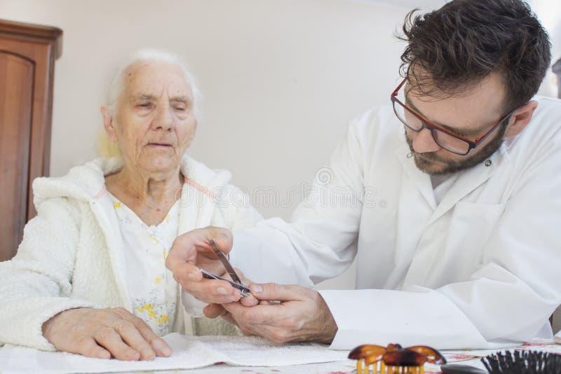 Sjukskötaresnitten spikar på händerna av en gammal kvinna royaltyfria bilder