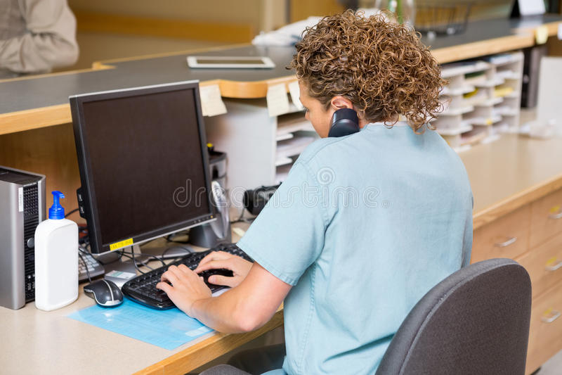 Sjuksköterska Answering Telephone While som arbetar på arkivbild