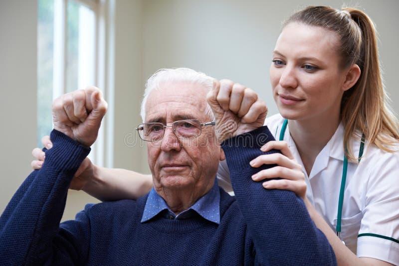 Sjuksköterska Assessing Stroke Victim, genom att lyfta armar arkivfoton