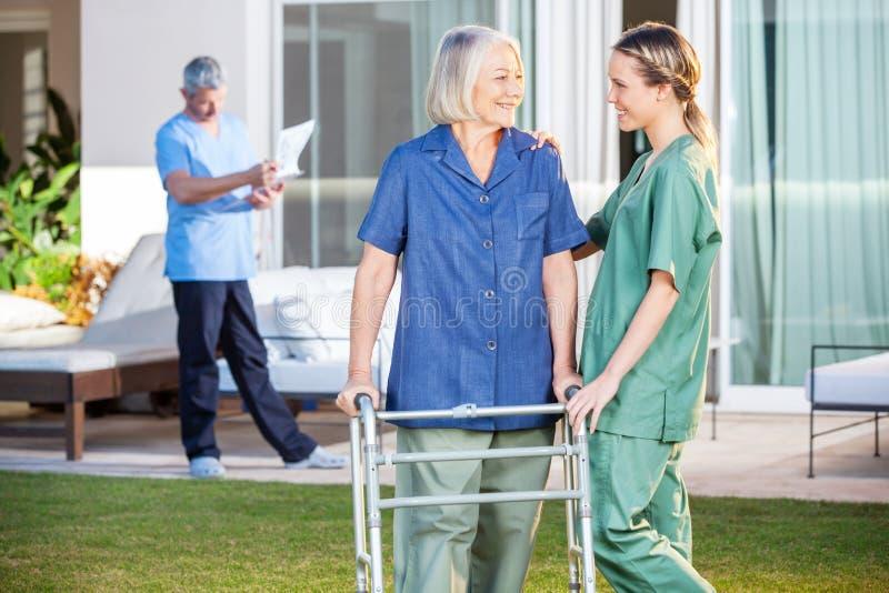 Sjuksköterska Assisting Senior Woman som går med Zimmer royaltyfria bilder