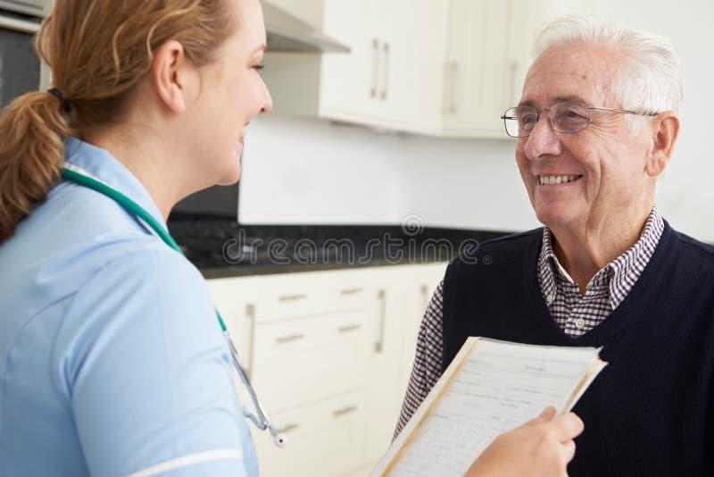 Sjuksköterska Discussing Medical Record med den höga manliga patienten royaltyfri fotografi