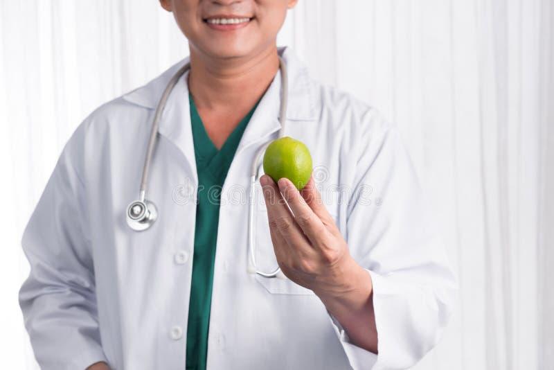 Sjuksköterska- eller mandoktor som ger le för äpple läkarundersökning för hälsa för omsorgscollageconcep royaltyfri bild