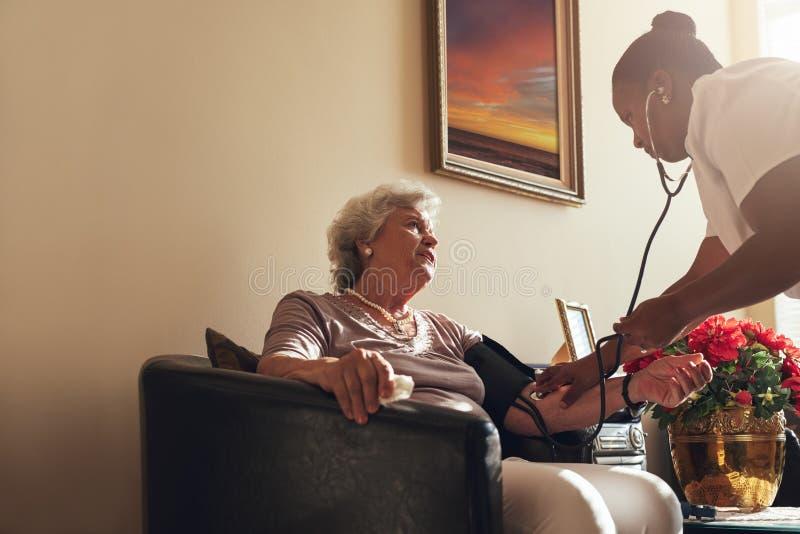 Sjuksköterska för hem- sjukvård som kontrollerar blodtryck av den höga kvinnan royaltyfria foton