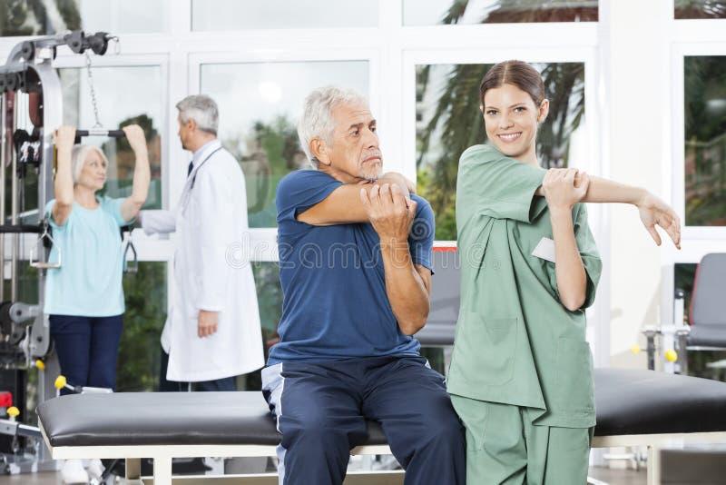 Sjuksköterska Guiding Senior Man, i sträckning av övning arkivbild