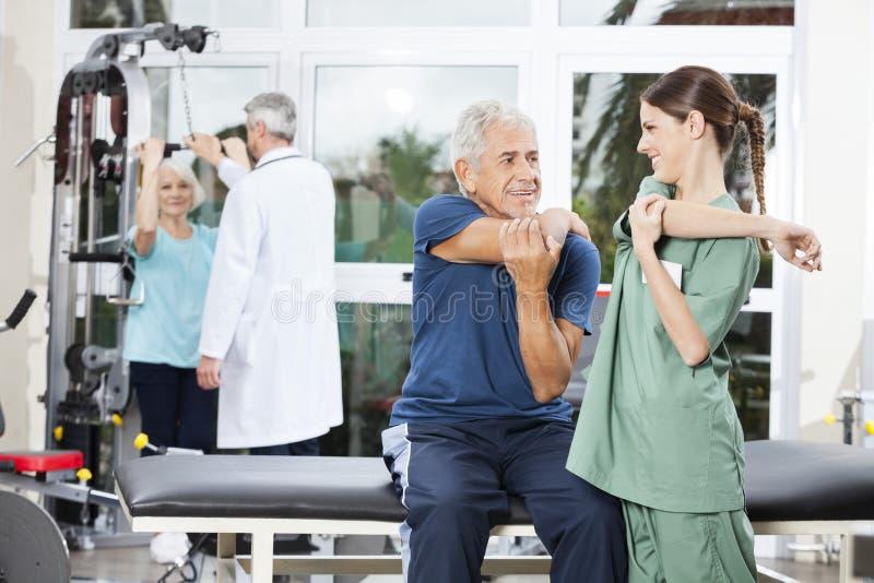 Sjuksköterska Guiding Senior Patient i armövning på Rehabmitten arkivfoton