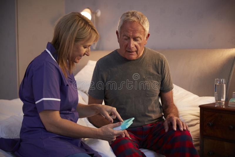 Sjuksköterska Helping Senior Man som organiserar läkarbehandlingen på hem- besök royaltyfri foto