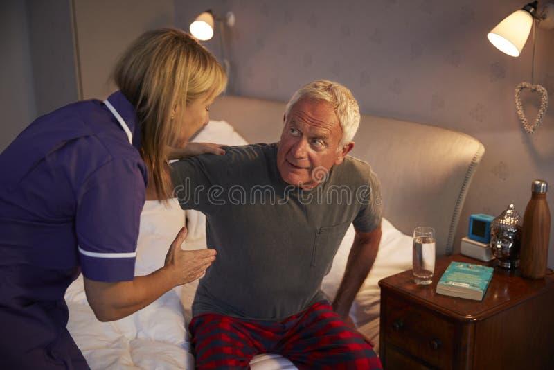 Sjuksköterska Helping Senior Man ut ur säng på hem- besök arkivfoto