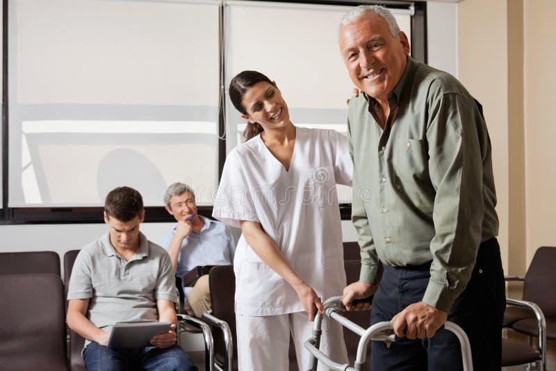 Sjuksköterska Helping Senior Patient med fotgängaren arkivbilder