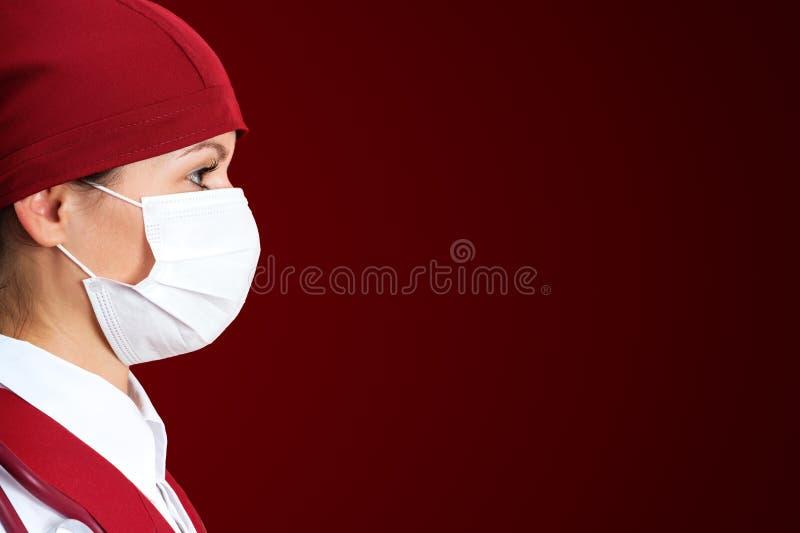 Sjuksköterska i maskering med röd bakgrund fotografering för bildbyråer