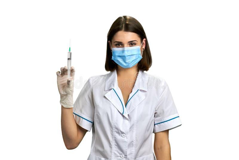 Sjuksköterska i medicinsk maskeringsinnehavinjektionsspruta royaltyfri bild