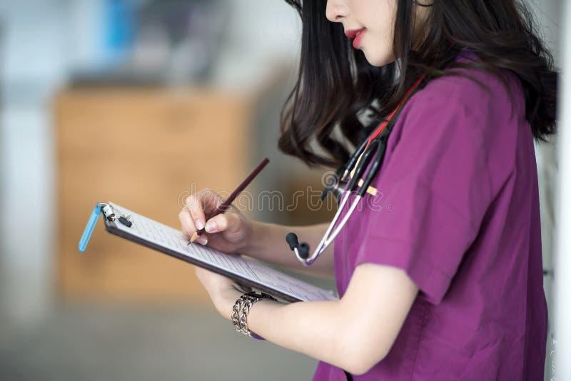 Sjuksköterska i purpurfärgat enhetligt anseende på tålmodigt rum och handstil arkivbild