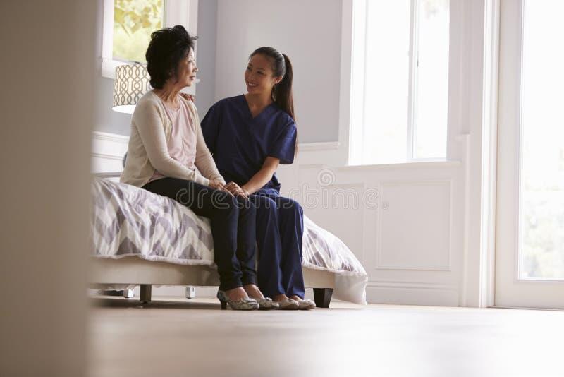 Sjuksköterska Making Home Visit till den höga kvinnan royaltyfri bild