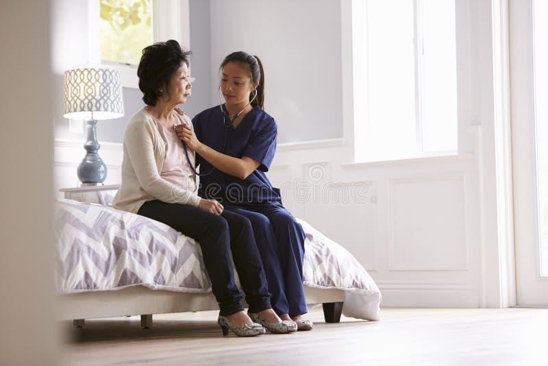 Sjuksköterska Making Home Visit till den höga kvinnan för medicinsk examen fotografering för bildbyråer