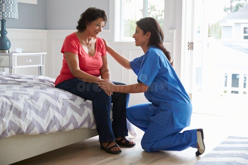 Sjuksköterska Making Home Visit till den höga latinamerikanska kvinnan fotografering för bildbyråer