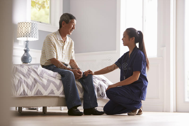 Sjuksköterska Making Home Visit till den höga mannen arkivfoto
