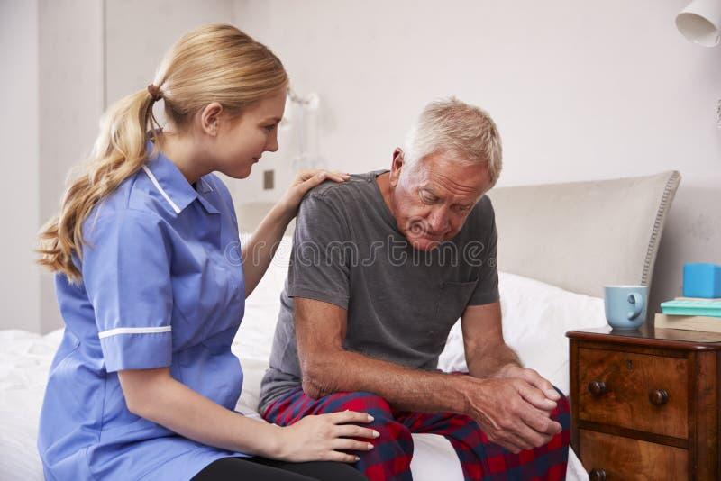 Sjuksköterska Making Home Visit till lidande för hög man med fördjupning arkivbilder