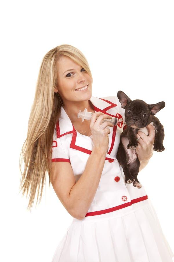Sjuksköterska med det lilla hundleendet som ger skottet arkivbilder