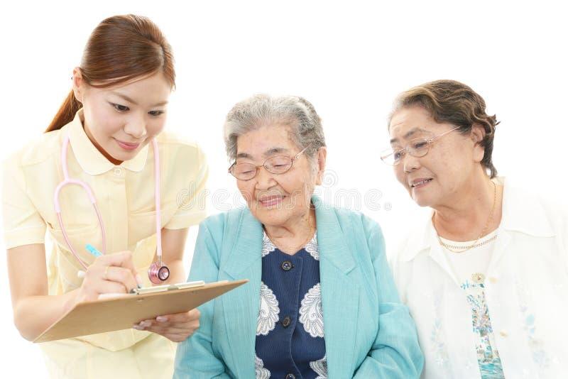 Sjuksköterska med gamla kvinnor royaltyfri foto