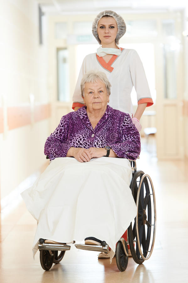 Sjuksköterska med gammalare tålmodig i rullstol royaltyfri bild