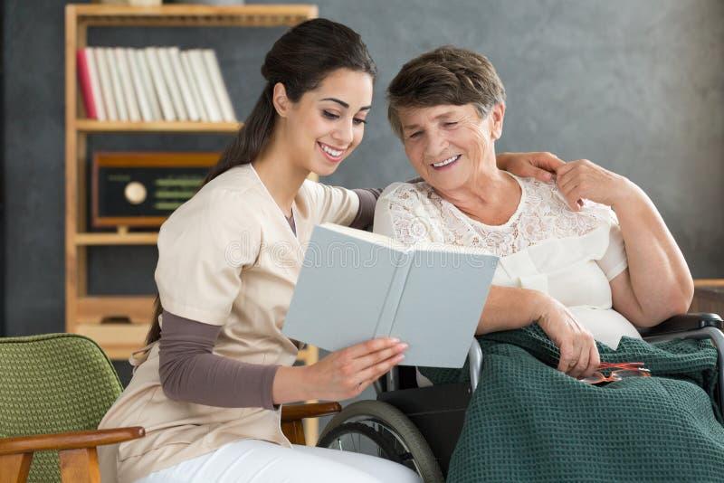 Sjuksköterska och kvinna som tillsammans läser royaltyfri bild
